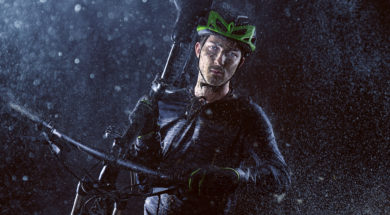 Mountainbiker carries his bike through the rain