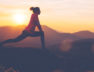 Silhouette of athletic girl doing stretching after a great jog in the mountains at sunset. Sport tight clothes.